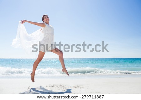 Peaceful brunette jumping at the beach