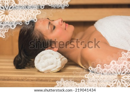 Peaceful brunette relaxing in a sauna against snowflake frame - stock photo