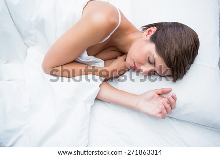Peaceful brunette sleeping at home in the bedroom