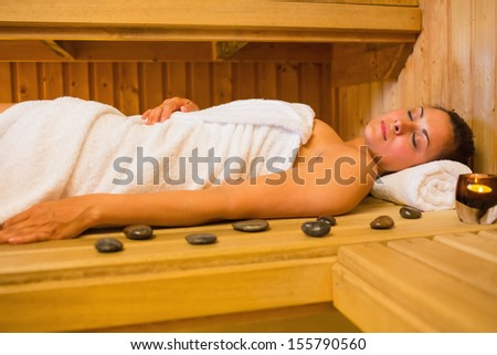 Peaceful brunette woman lying in a sauna with pebbles and candle