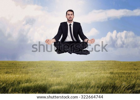 Peaceful businessman sitting in lotus pose relaxing against nature scene - stock photo