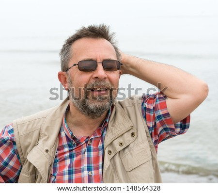 Peaceful carefree elderly man on the sea background