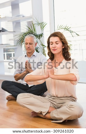 Peaceful casual business colleagues meditating in the office - stock photo