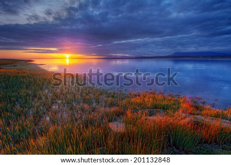 Peaceful colorful blue and orange river sunset with bright grass - stock photo