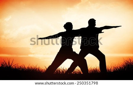 Peaceful couple in white doing yoga together in warrior position against orange sunrise - stock photo