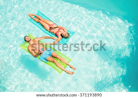 Peaceful couple on lilos holding cocktails in the pool - stock photo