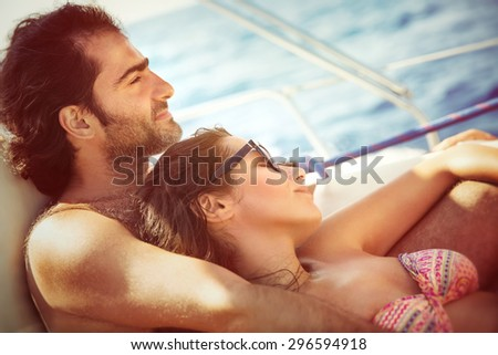 Peaceful couple relaxing on sailboat, lying down on the deck and enjoying tranquil summer trip on water transport, pleasure and enjoyment from romantic relationship  - stock photo