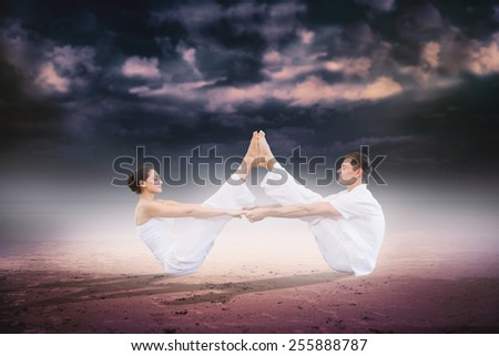 Peaceful couple sitting in boat position together against dark cloudy sky