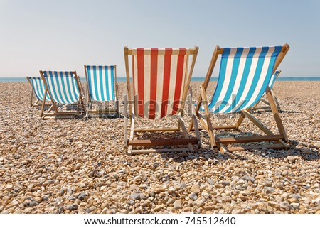 Peaceful Day On The Pebble Beach, Classic Red And Blue Deckchairs, Blue Sea  In