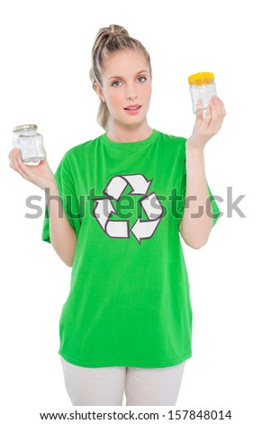 Peaceful environmental activist wearing recycling tshirt holding jars on white background - stock photo