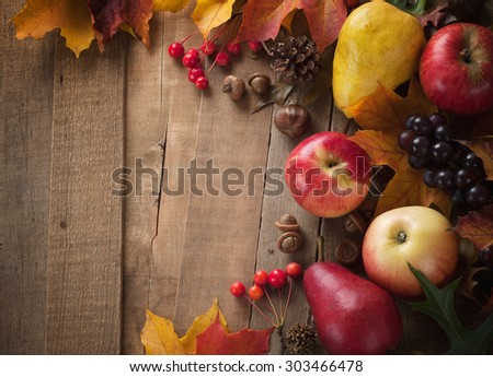 Peaceful Fall Fruit, Leaf, Acorn Still Life arrangement on Rustic Wood Board Table Background with room or space for copy, text, your words.  Horizontal dark, warm tone, looks good as vertical. - stock photo