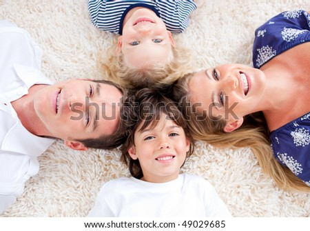 Peaceful family lying in circle on the wall-to-wall carpet at home