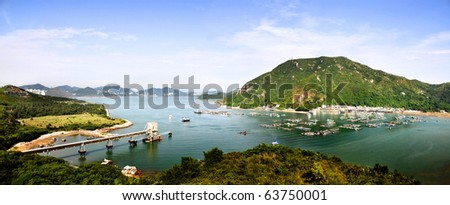 Peaceful fishing village on the shore with green mountains in the background and a clear blue sky. - stock photo