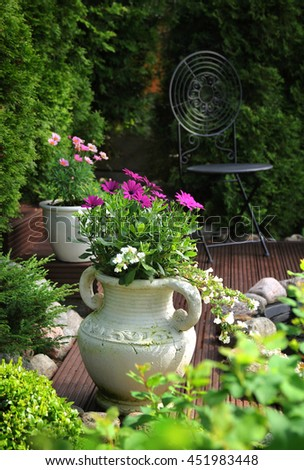 Peaceful garden patio feeling with flowers in clay pots - stock photo