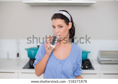Peaceful gorgeous model drinking water in bright kitchen - stock photo