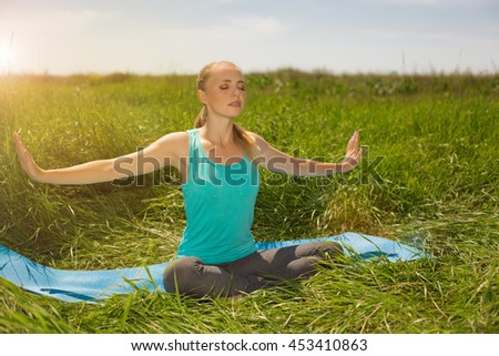 peaceful healthy fit blond young woman meditating on the nature with  closed  eyes