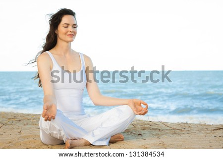 Peaceful healthy & fit young woman meditating on the beach - stock photo