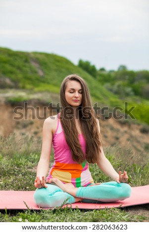 Peaceful healthy & fit young woman meditating on the nature with eyes closed