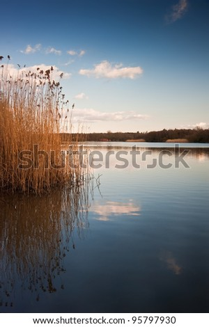 Peaceful image of calm lake landscape with vibrant sky and colors - stock photo
