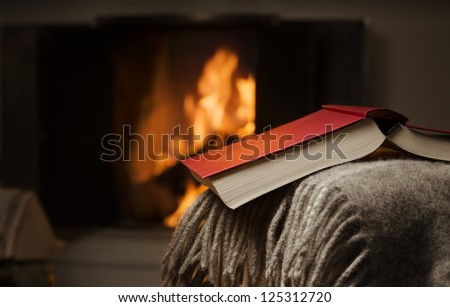 Peaceful image of open book resting on a arm rest of a couch. Warm fireplace on background. - stock photo
