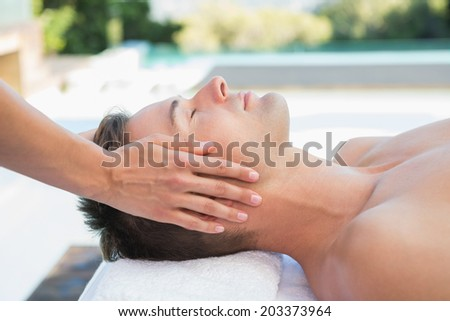 Peaceful man getting a head massage poolside outside at the spa - stock photo