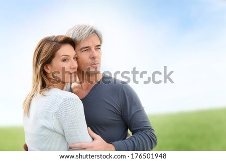 Peaceful middle-aged couple in countryside - stock photo