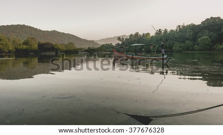Peaceful morning scene of calm lake and fisherman in his boat, India - stock photo