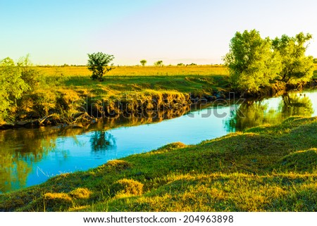 Peaceful nature scene of a beautiful creek at dawn. - stock photo
