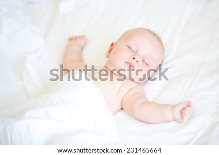 Peaceful newborn baby lying on a bed sleeping on white sheets - stock photo