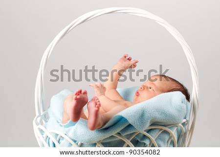 Peaceful newborn baby sitting in a blanket-lined basket. - stock photo