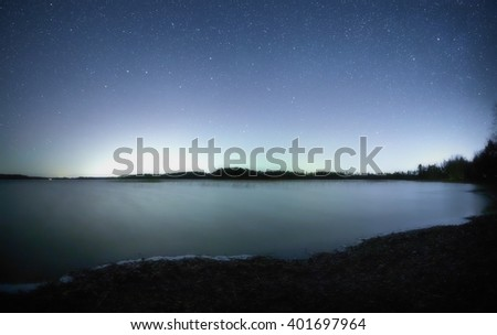 Peaceful night scene with starry sky at a lake in Finland. Reflection of stars on the still water of the lake. - stock photo