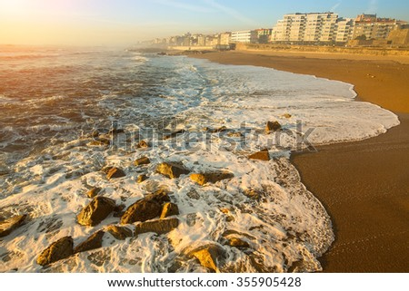 Peaceful ocean surf on the beach of Porto, Portugal. - stock photo