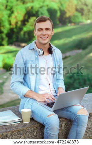 Peaceful place for studying. Male student working on laptop and smiling while sitting outdoors with books and coffee
