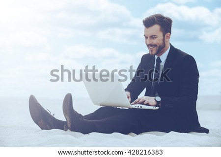 Peaceful place to work. Cheerful young man in formalwear working on laptop while sitting on sand in desert