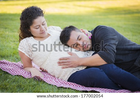 Peaceful Pregnant Hispanic Couple in The Park Outdoors.