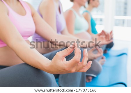 Peaceful pregnant women meditating in yoga class in a fitness studio - stock photo