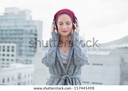 Peaceful pretty blonde listening to music outdoors on urban background - stock photo
