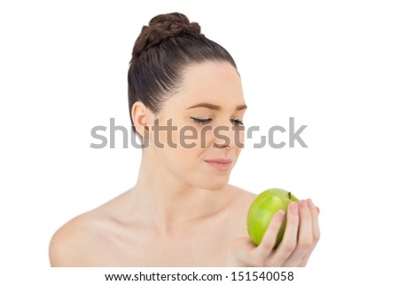 Peaceful pretty model holding apple while posing on white background