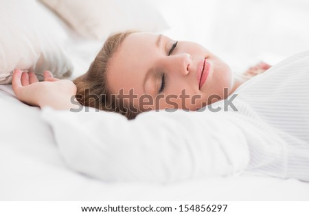 Peaceful pretty woman sleeping on her bed in a bedroom
