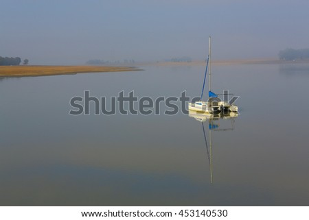 Peaceful quiet and still yacht or boat on a tranquil and misty lake or dam in the early morning countryside