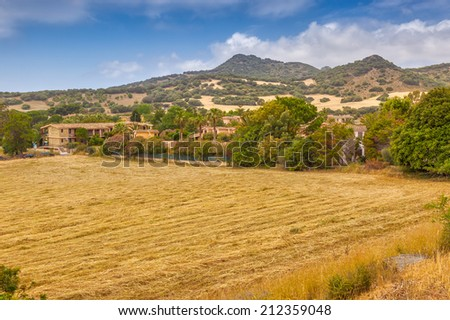 Peaceful rural landscape with mown field in front captured at Villasimius, Sardinia, Italy - stock photo