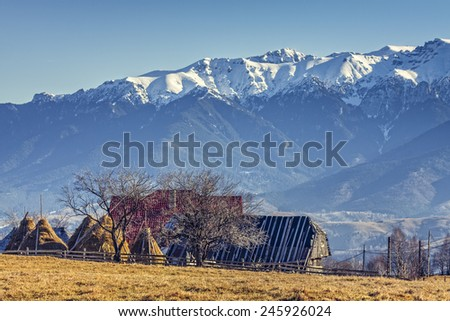 Peaceful rural landscape with traditional Romanian mountainous farm with old barn and haystacks, near Bucegi massif in Moeciu, Brasov county, Romania. Travel destinations. - stock photo
