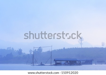 peaceful scene of lake with pier on water at morning with fog