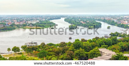 Peaceful scenery on river with boat glides on water, distance small houses with red tile roofs, river turn right back from making a painting of Hue ancient capital poetic today