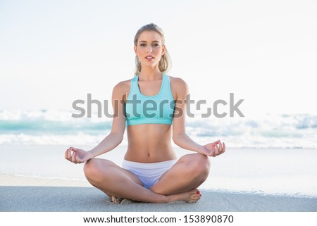 Peaceful slender blonde in sportswear meditating on a sunny beach - stock photo