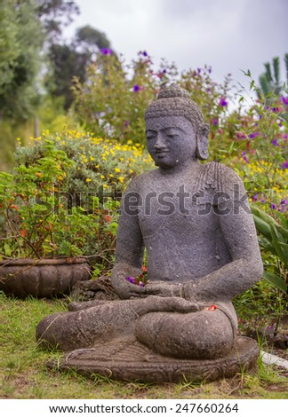 Peaceful Stone Garden Buddha Surrounded by Flowers - stock photo
