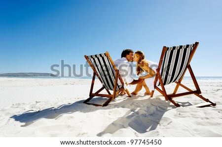 peaceful summer beach couple kissing while enjoying the sunshine on a pristine coastline. - stock photo
