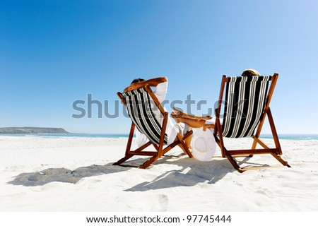 peaceful summer beach couple sitting and relaxing enjoying the sunshine on a pristine coastline
