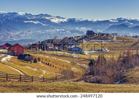 Peaceful sunny rural landscape with alpine hamlet and wide grasslands in Pestera village, Brasov county, Romania. Bucegi mountains range on the hazy horizon. - stock photo