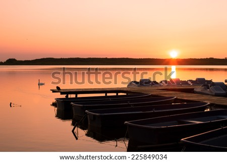 Peaceful Sunset at the Lakeshore with Jetty and Row Boats - stock photo